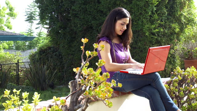 ms young woman sitting in garden using laptop / sherman oaks, california, usa.   - see other clips from this shoot 1655 stock videos & royalty-free footage