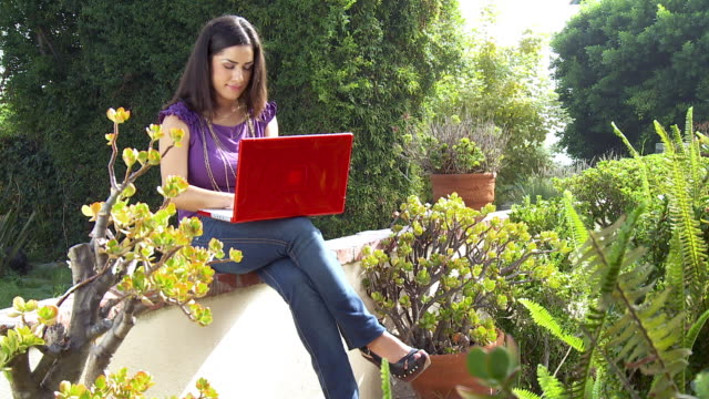 ws young woman sitting in garden using laptop / sherman oaks, california, usa.   - see other clips from this shoot 1655 stock videos & royalty-free footage