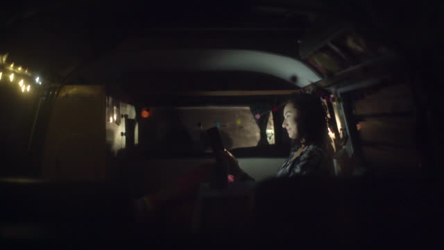 young woman sitting in her camper van at night - avventura video stock e b–roll