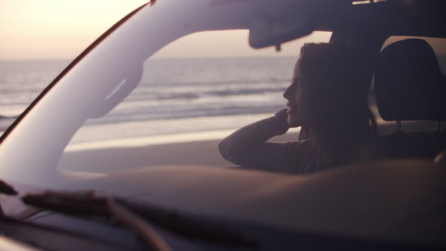 vidéos et rushes de young woman sitting in her car at the beach - café boisson