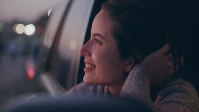vidéos et rushes de young woman sitting in her car looking out the window - stationary