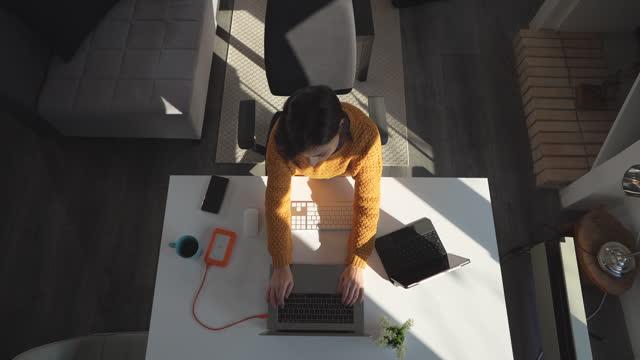 vídeos y material grabado en eventos de stock de mujer joven sentada en la sala de estar y trabajando en el ordenador portátil desde casa - table top view