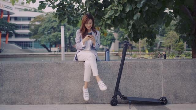 年輕女子坐在公園與電動滑板車使用手機 - 全身 個影片檔及 b 捲影像