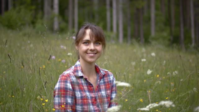 vidéos et rushes de jeune femme s'asseyant dans l'herbe haute regardant et souriant à l'appareil-photo - sitting