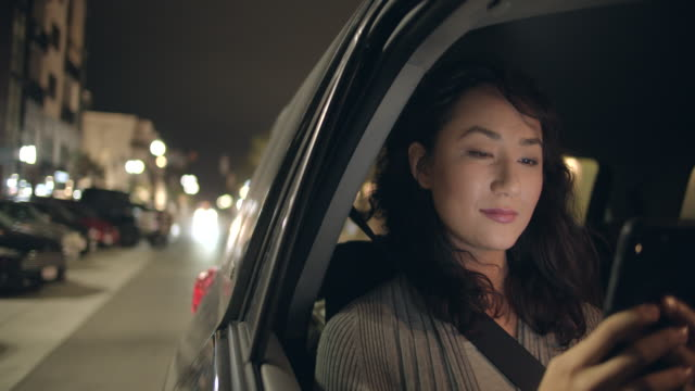 vidéos et rushes de young woman sitting in the back seat of a car at night - ceinture de sécurité