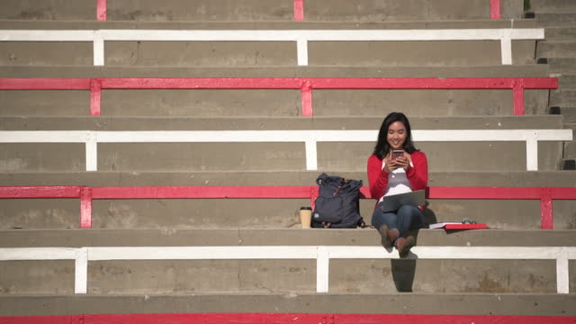 WS Young woman sitting in the bleachers using her smart phone