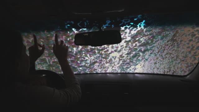 ung kvinna som sitter i bilen vid den automatiska biltvätten, när bilen städar. tvättmedel appliceras. utsikt från bilen genom vindrutan. - biltvätt bildbanksvideor och videomaterial från bakom kulisserna