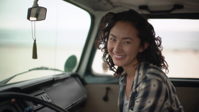 Young woman sitting in the front seat of her camper van