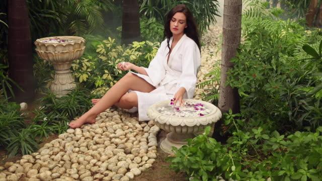vídeos de stock, filmes e b-roll de young woman sitting in the garden in the farm house, delhi, india - health farm