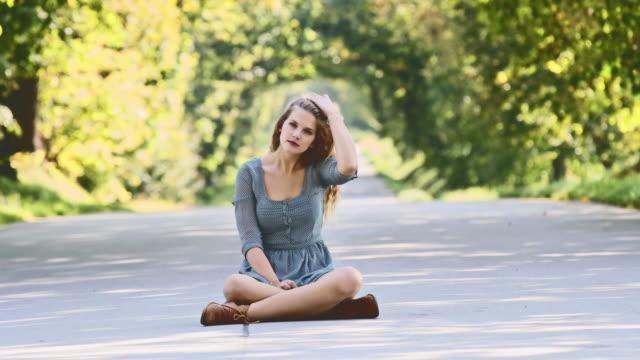 SLO-MO-DS-junge Frau sitzt in der Mitte einer Straße
