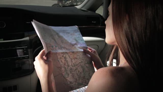 cu young woman sitting inside car, looking at map and outside woman in hot pants working on bike / palmdale, ca, united states   - palmdale stock videos and b-roll footage