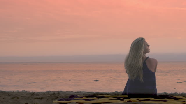 young woman sitting on a beach at sunset watching pacific ocean uhd - vesper stock stock videos & royalty-free footage