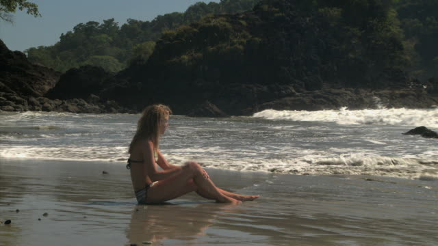 young woman sitting on a beach - see other clips from this shoot 1157 stock videos & royalty-free footage