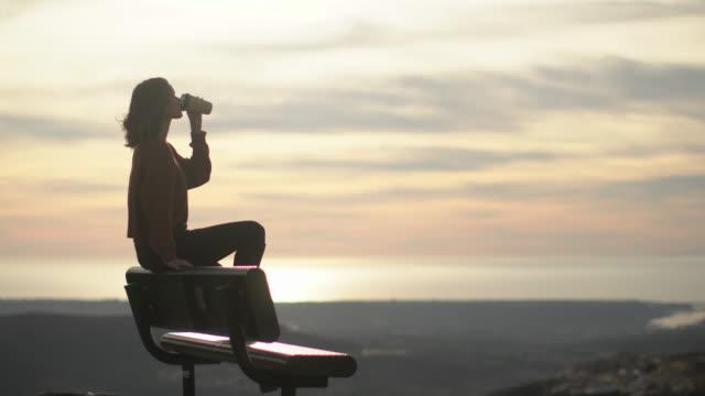 vidéos et rushes de ws young woman sitting on a park bench drinking coffee . - café boisson