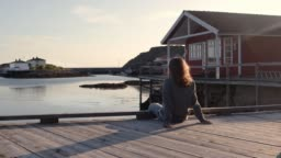 A young woman sitting on a pier at sunset time and enjoys the view.