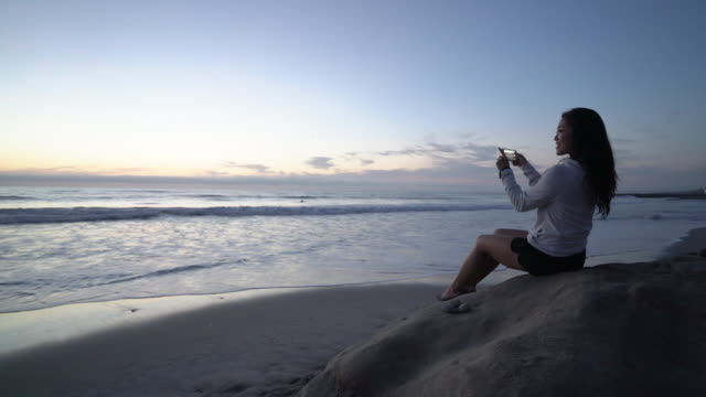 WS SM Young woman sitting on a rock taking a photo of the ocean