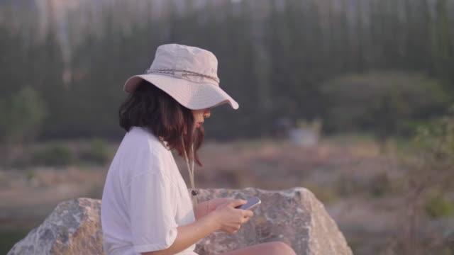 vídeos de stock, filmes e b-roll de jovem sentada em um rochoso na natureza em um dia ensolarado. - artigo de vestuário para cabeça