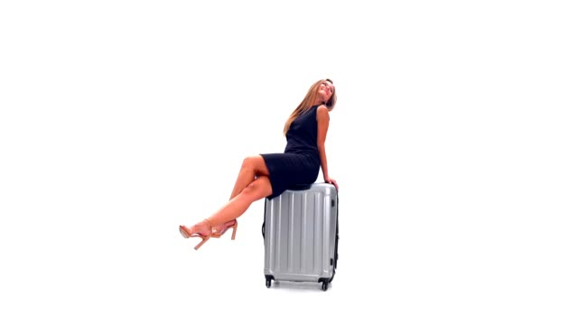 Young woman sitting on a suitcase and posing