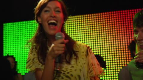 ms zo slo mo young woman sitting on bar singing karaoke / london, uk - singing stock videos & royalty-free footage