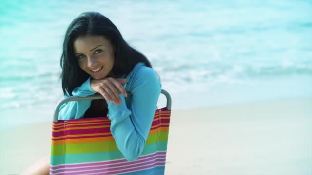 vídeos y material grabado en eventos de stock de cu young woman sitting on beach chair next to the ocean - mano en la barbilla