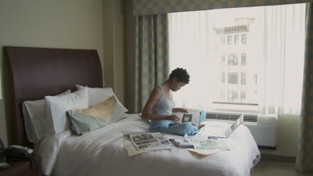 WS Young woman sitting on bed using laptop / New York City, New York, USA.