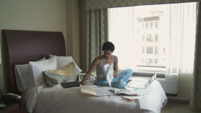 CU Young woman sitting on bed with documents, using laptop / New York City, New York, USA.