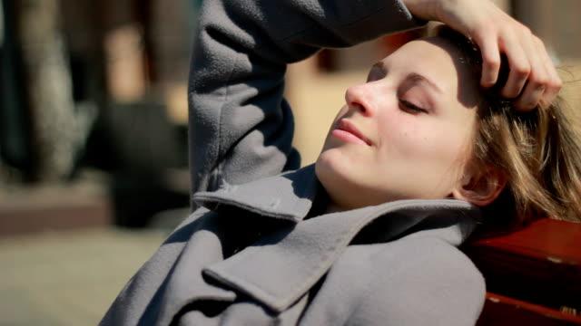 座る若い女性のベンチ屋外笑顔を探します。 - オーバーコート点の映像素材/bロール
