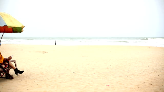 young woman sitting on deck chair on calangute beach and using smartphone, goa - outdoor chair stock videos & royalty-free footage