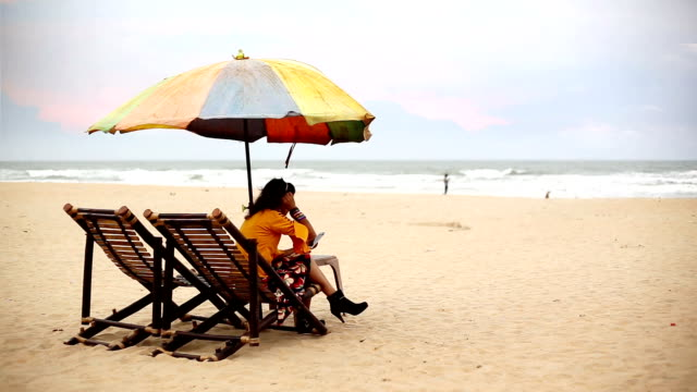young woman sitting on deck chair on calangute beach and using smartphone, goa - goa stock videos & royalty-free footage