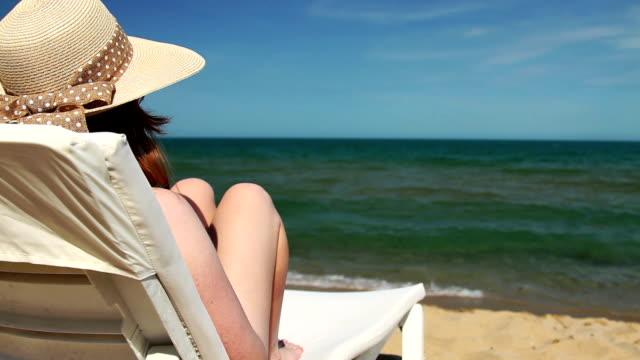 vídeos de stock, filmes e b-roll de jovem mulher sentada na espreguiçadeira na praia - espreguiçadeira