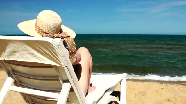 young woman sitting on deck chair on the beach - outdoor chair stock videos and b-roll footage