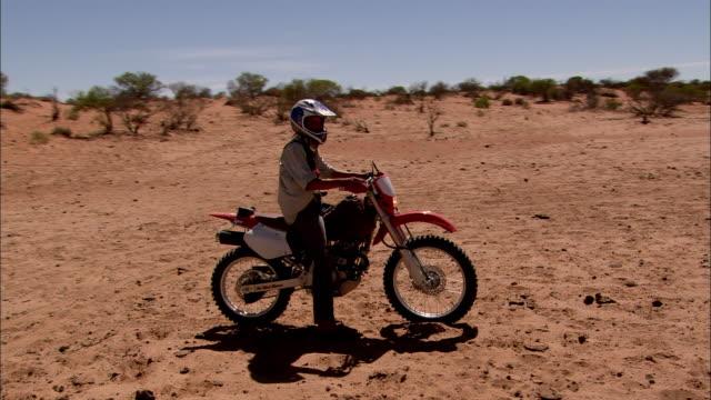 vidéos et rushes de ws ds young woman sitting on dirt bike in desert landscape, anna creek, south australia, australia - seulement des jeunes femmes