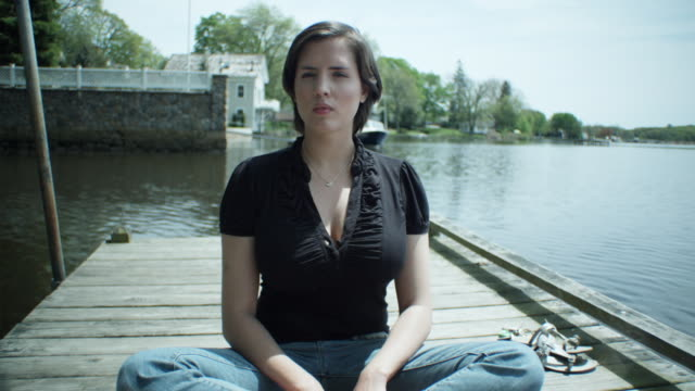 ms young woman sitting on dock with stern expression towards camera, essex, connecticut, usa - bootssteg stock-videos und b-roll-filmmaterial