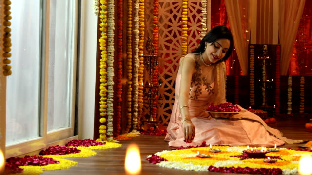 MS PAN Young woman sitting on floor and making rangoli with flower petals during diwali festival / Delhi, India