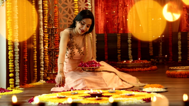 MS Young woman sitting on floor and making rangoli with flower petals during diwali festival / Delhi, India