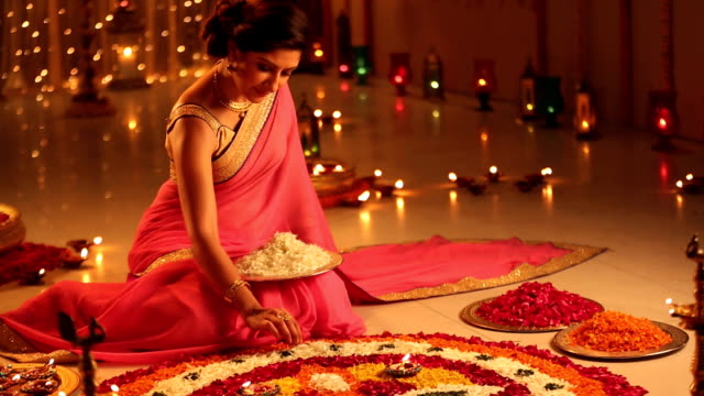 MS PAN Young woman sitting on floor and making rangoli with petals during diwali festival