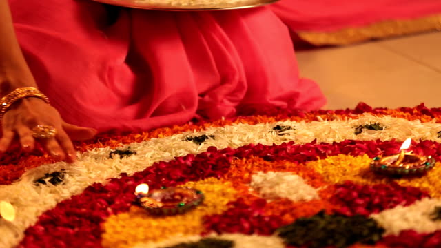 CU PAN Young woman sitting on floor and making rangoli with petals during diwali festival