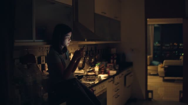 young woman sitting on kitchen counter and using smartphone standing in kitchen at home in midnight. - text stock videos & royalty-free footage