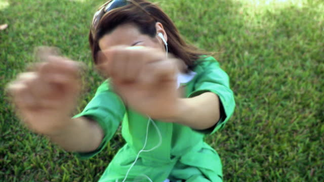 ms young woman sitting on lawn, laughing and dancing to music on headphones / south beach, florida - mp3プレイヤー点の映像素材/bロール