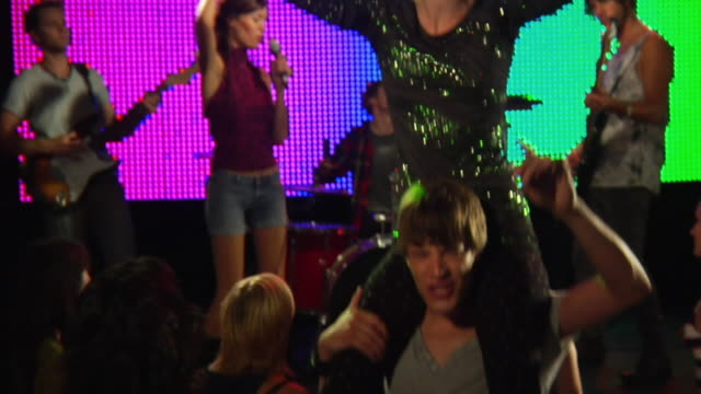 ms slo mo young woman sitting on man's shoulders at rock concert / london, uk - shoulder ride woman stock videos & royalty-free footage