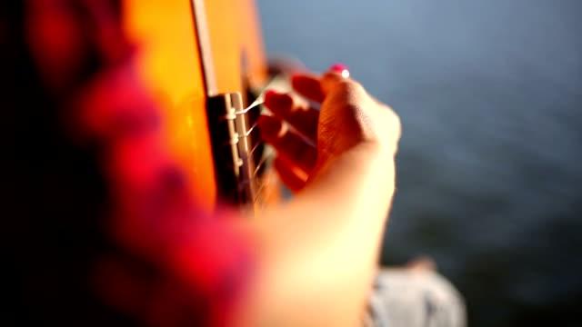 vídeos de stock, filmes e b-roll de jovem mulher sentada no cais e tocar violão - violão acústico