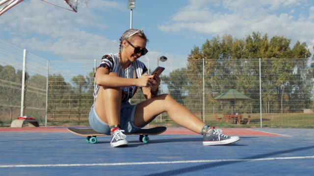 vídeos de stock e filmes b-roll de young woman sitting on skateboard on basketball court and texting while taking a rest - 25 29 anos