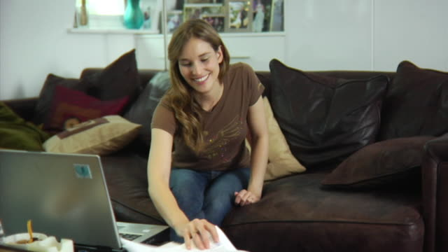 slo mo ms young woman sitting on sofa, doing paperwork / london, united kingdom - see other clips from this shoot 1518 stock videos & royalty-free footage