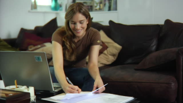 SLO MO MS Young woman sitting on sofa, using laptop and doing paperwork / London, United Kingdom