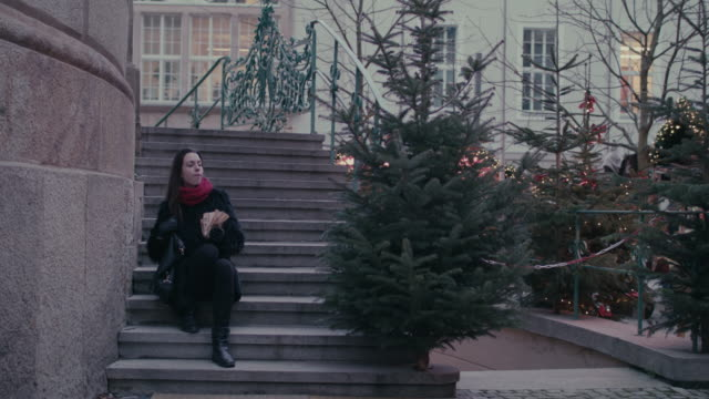 young woman sitting on stone steps taking a break from shopping at christmas market - steps and staircases点の映像素材/bロール