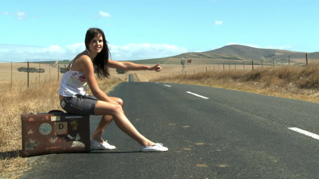 WS Young woman sitting on suitcase and hitchhiking / Cape Town, South Africa