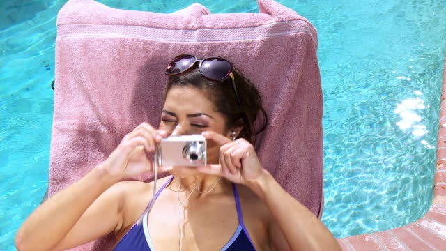 ms young woman sitting on sunlounger photographing with digital camera / sherman oaks, california, usa. - digital camera stock videos & royalty-free footage