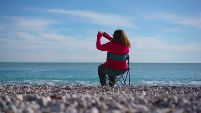 junge frau sitzt am strand, fotografiert, 4k video - dicke frauen am strand stock-videos und b-roll-filmmaterial