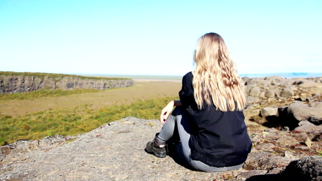 young woman sitting on the cliff edge in iceland - horseshoe stock videos and b-roll footage