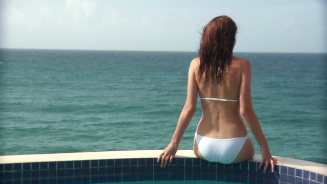 MS RV Young woman sitting on the edge of swimming pool, tossing her hair and looking back to smile at camera/ Scarborough, Tobago, Trinidad and Tobago